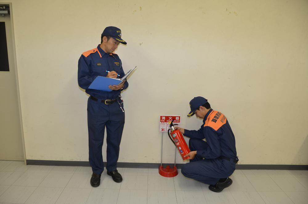 2人で消火器の点検を行う消防士の写真