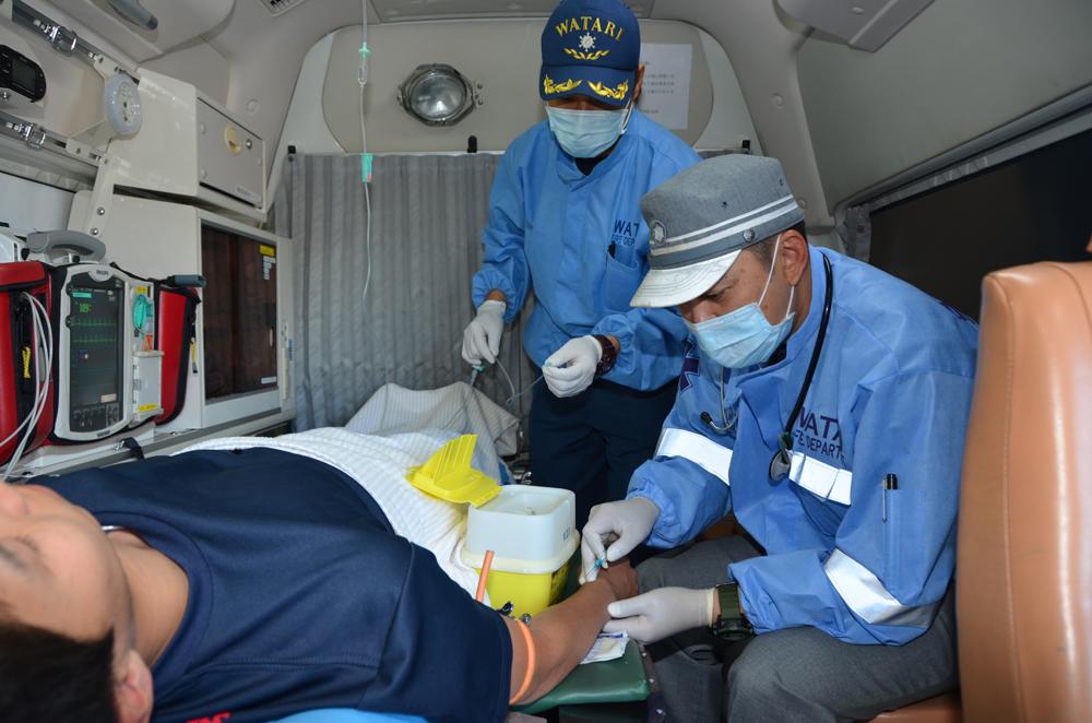 救急車の中で応急処置(点滴)の訓練を行う消防士の写真