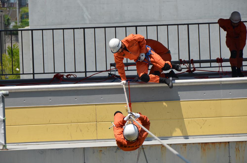 高所からロープを伝って移動する訓練を行う消防士の写真