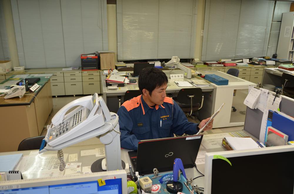 パソコンに向かい資料を見ながら書類作成を行う消防士の写真