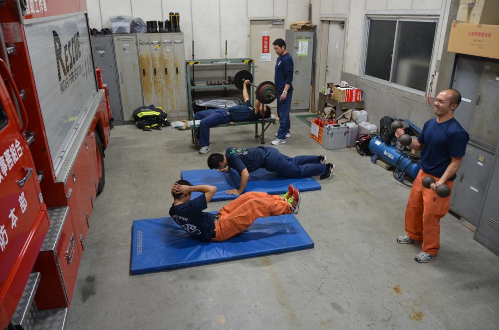 筋力トレーニングを行う消防士達の写真