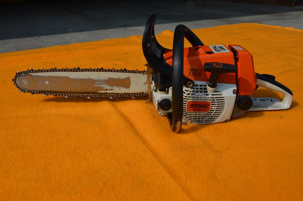 チェーンソーの写真(持ち手のついたエンジンの先端にチェーンで回転するノコギリの刃の様な物がついている)