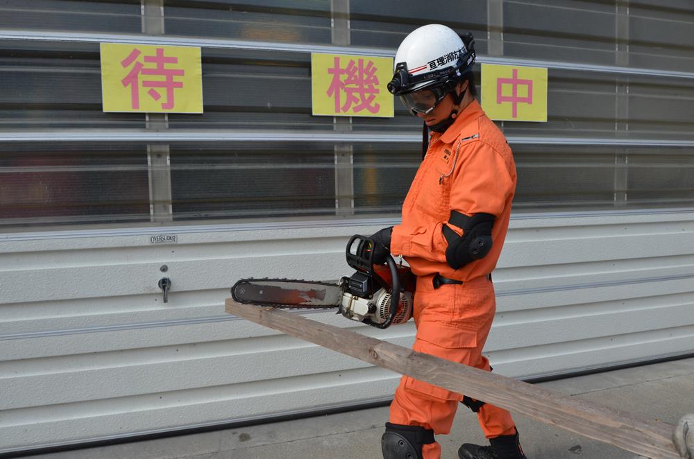 チェーンソーを使用している写真(消防士が両手でチェーンソーを持ち、木材を切ろうとしている)