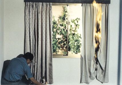 カーテンの写真(左に火がついていない防炎カーテン、右に火が燃え広がり天井に火の高さが達してしまっている非防炎カーテン)