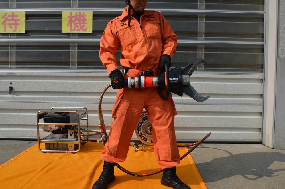 カッターを両手で持つ消防士の写真(先端が開いており、消防士の腰上辺りから太もも辺りまで開いている)