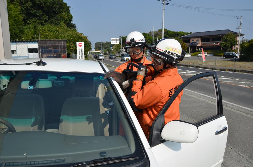 カッターを使用している写真(消防士2人がかりで抱え、車のドアの縁からフロントガラスにかけてを切ろうとしている)