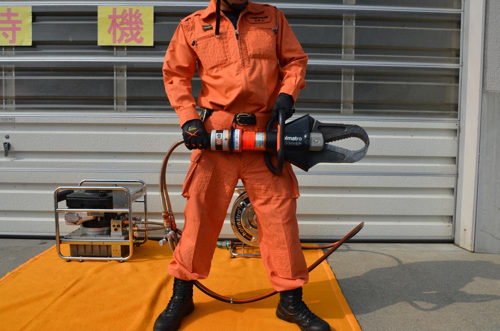 カッターを両手で持つ消防士の写真(消防士の頭3つ分くらいの大きさがあり、先端は閉じている)