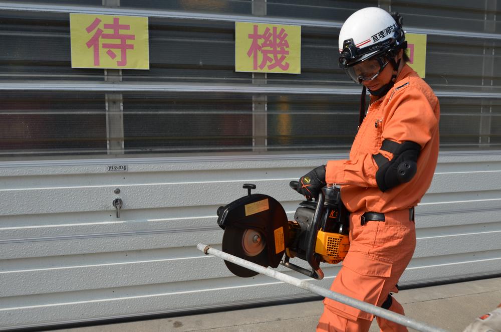 エンジンカッターを使用している写真(消防士がエンジンカッターを両手で持ち鉄パイプを切ろうとしている)