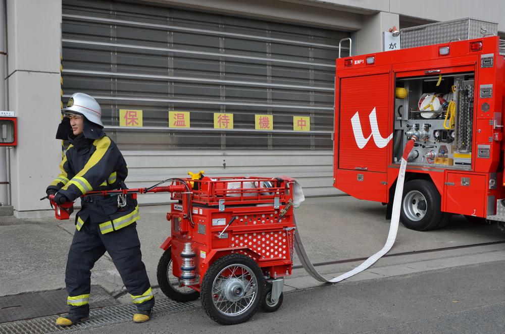 ホースカーを使用している写真(消防車から伸びたホースがホースカーに繋がり先頭にはホースカーのハンドルを握る消防士)