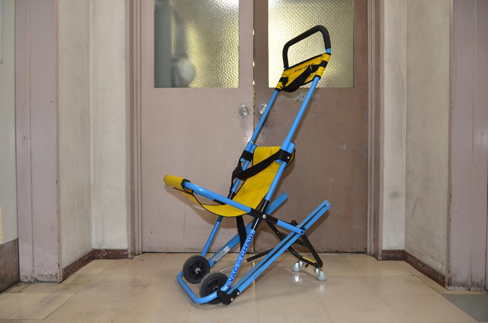 階段搬送用器具の写真(椅子型の担架の様なもので、前に大きい車輪、後ろに小さい車輪がついている)