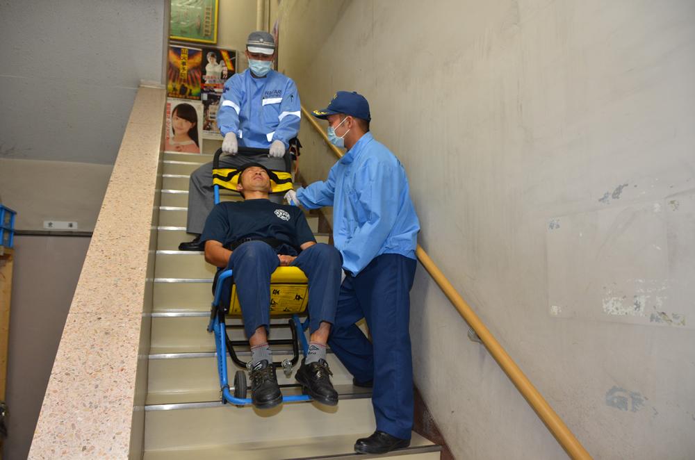 階段搬送用器具を階段で使用している写真(男性が階段搬送用器具に乗っており、前1人横1人の消防士がしっかりと器具を持って支え階段を下っている)