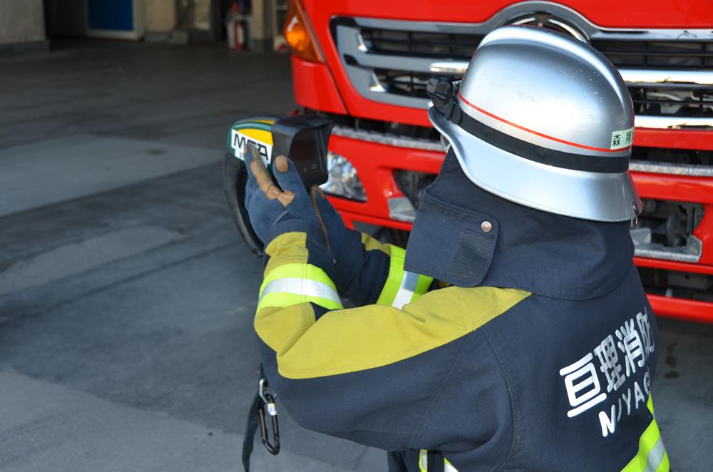熱画像直視装置を使用した写真(消防士が両手で装置を握り画面を見ている)