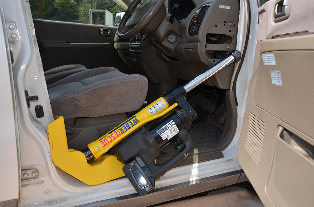 ラムを使用している写真(車の運転席のドア縁をラムで押し広げている)