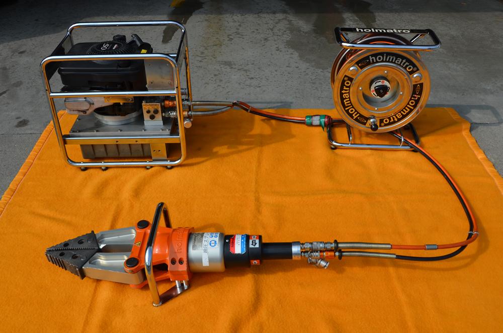 スプレッダーの写真(エンジンとホースで繋がっており本体は巨大なペンチの先の様な形をしている)