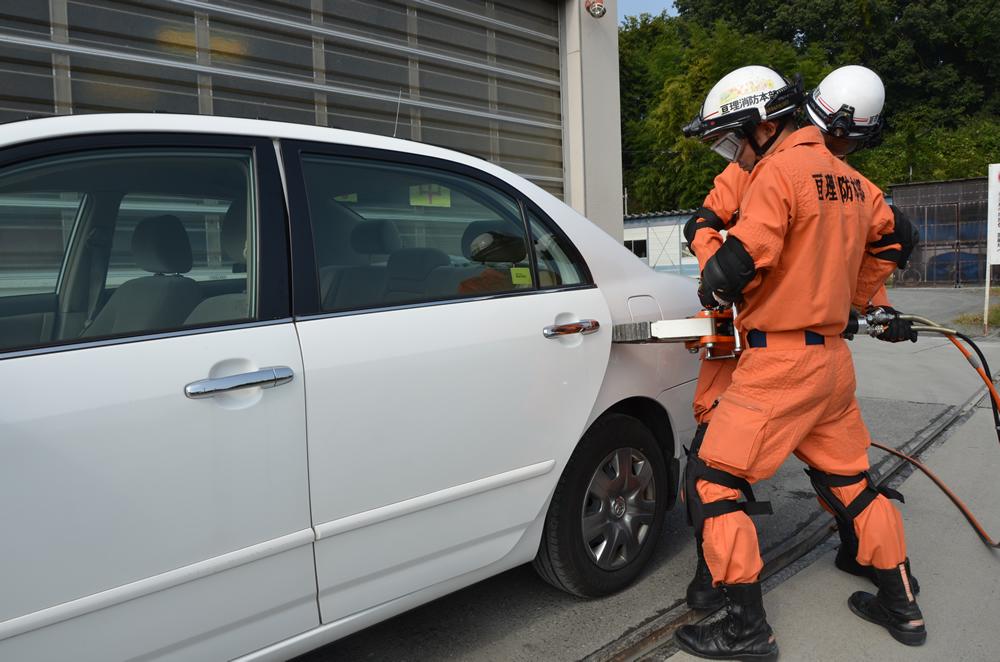 スプレッダーを使用している写真(消防士2人がかりでスプレッダーを抱え車の後部座席のドアをこじ開けている)