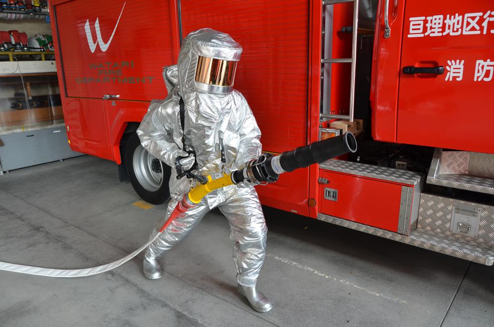 肌を一切露出しない耐熱服を身にまといホースを構える消防士の写真