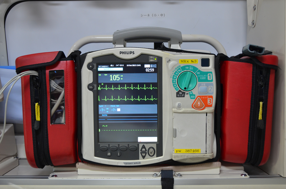 除細動器の写真(小型の機械にボタンやモニターがついており、機械の両サイドにはパットやコードなどが入るポケットが取り付けられている)