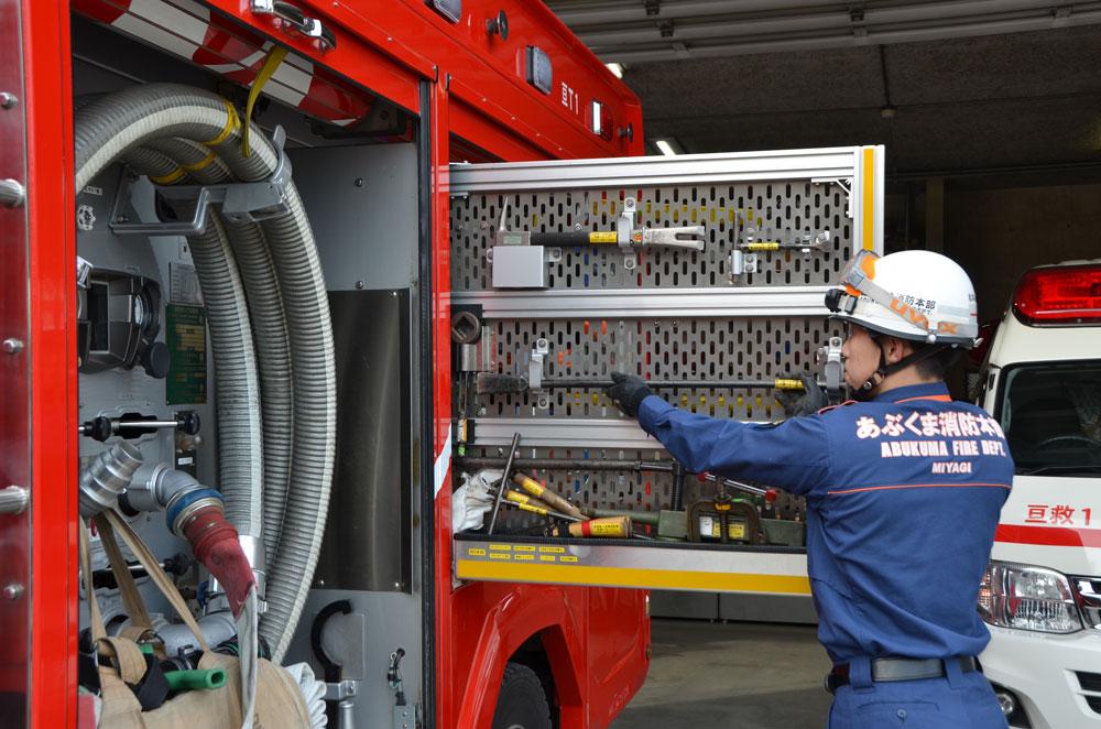 消防車に積んである道具の確認を行っている消防士の写真