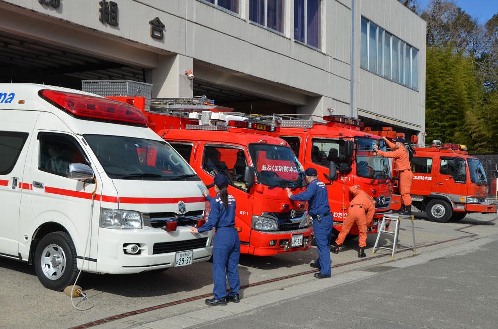 消防車や救急車を綺麗に掃除する消防士達の写真
