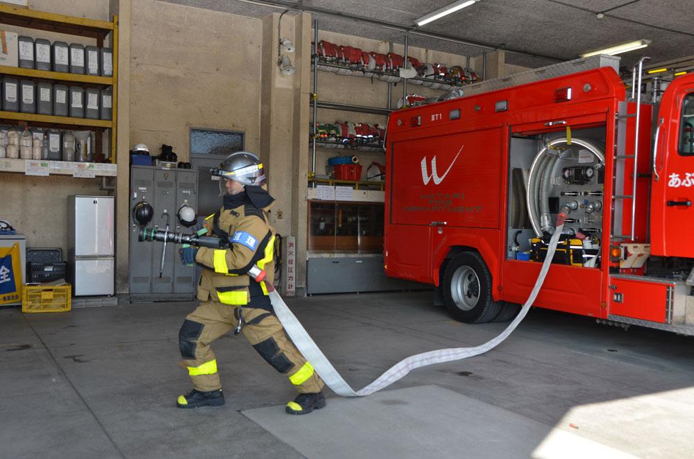 管槍を使用した状況の写真(消防士が管槍を取り付けたホースをしっかり抱えて構えている)