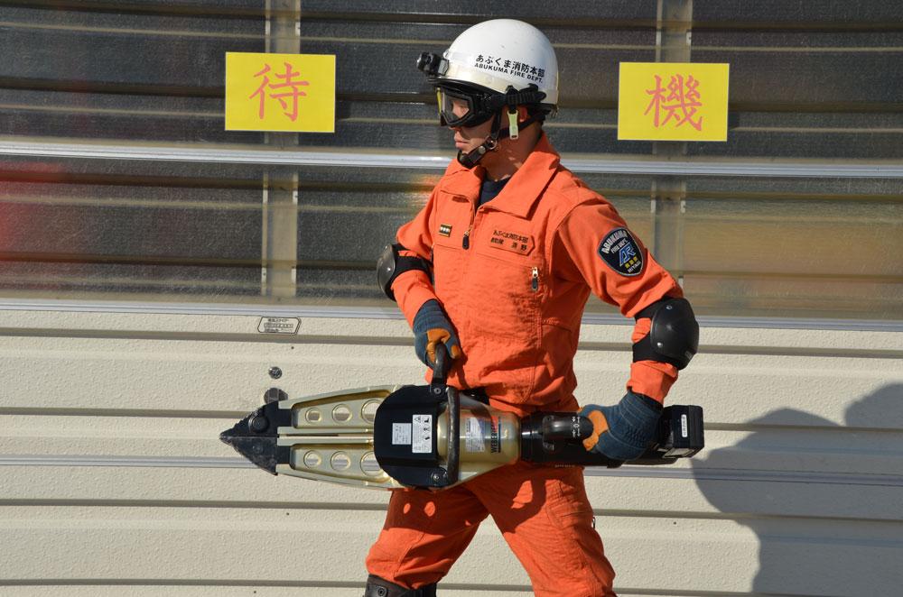 スプレッダーを両手で持つ消防士の写真(本体は消防士の頭3つ分くらいのサイズで、先端は閉じている)