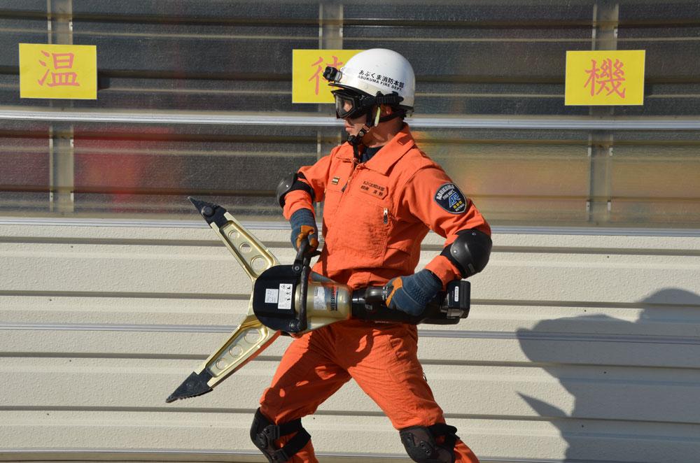 スプレッダーを両手で持つ消防士の写真(先端が開いており、消防士の胸の位置から膝の位置くらいまで開いている)
